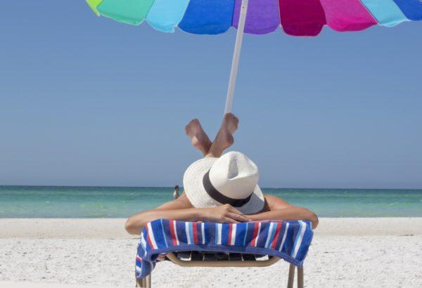 Woman in sunhat lounging on Anna Maria Island beach in beach chair