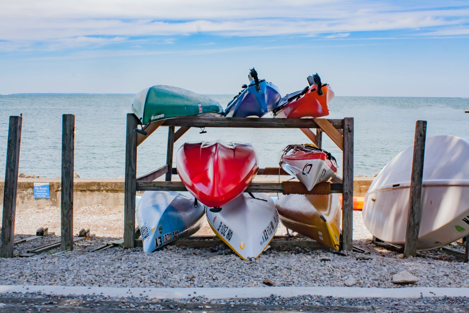 Large rack of kayaks, canoes, and beach equipment rentals by the ocean.